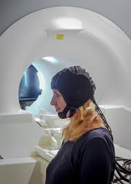 Two ways to record brain signals. Image of an MRI machine and a participant wearing an fNIRS cap.